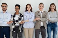 Счастливые разнообразные люди стоя держащ руки совместно стоковые фото
