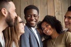 Счастливые разнообразные черно-белые люди собирают усмехаясь toget выпуска облигаций стоковые фотографии rf