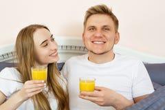 Счастливые расслабленные молодые пары с апельсиновым соком в кровати дома Романтичные пары выпивая апельсиновый сок лежа на их кр стоковая фотография rf