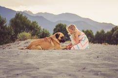 Счастливые ребенк и собака в песчаном пляже стоковое фото rf