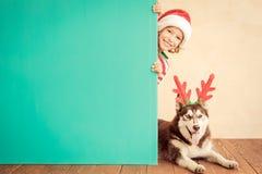 Счастливые ребенок и собака на Рожденственской ночи Стоковые Изображения RF