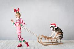 Счастливые ребенок и собака на Рожденственской ночи стоковая фотография rf