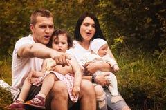 Счастливые родители и 2 дет совместно, outdoors Стоковые Фотографии RF