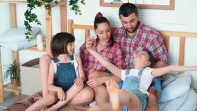 Счастливые родители и 2 дочери имеют полезного время работы совместно дома, сидят на кровати сток-видео