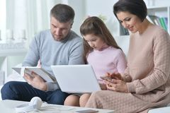 Счастливые родители и дочь используя цифровые приборы стоковые фото