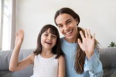 Счастливые руки дочери мамы и ребенк развевая смотря камеру стоковые изображения