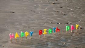 Счастливые свечи письма дня рождения в песке стоковая фотография