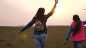 Счастливые сестры девушки, который побежали с самолетом игрушки на заходе солнца на поле Концепция счастливой семьи дети играют и сток-видео