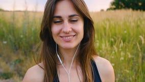 Счастливые смартфон пользы молодой женщины и положение наушников в поле на заходе солнца, здоровом образе жизни Использование бег сток-видео