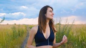 Счастливые смартфон пользы молодой женщины и положение наушников в поле на заходе солнца, здоровом образе жизни Использование бег видеоматериал
