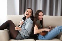 Счастливые смеясь над сестры на кресле в живущей комнате Стоковое Фото