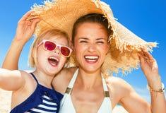 Счастливые современные мать и ребенок на береге моря принимая selfie Стоковое фото RF