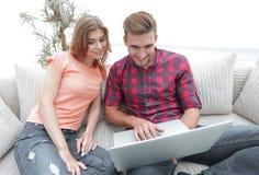 Счастливые современные пары занимаясь серфингом сеть и работая на компьтер-книжке дома Стоковое Изображение