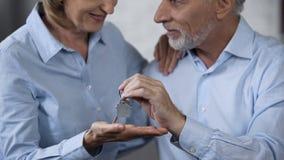 Счастливые старея пары держа ключи дома, мечты приходят истинный, вклад в приобретении стоковые изображения rf