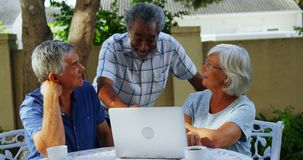 Счастливые старшие друзья взаимодействуя друг с другом пока использующ компьтер-книжку 4k видеоматериал