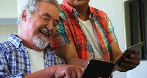 Счастливые старшие друзья используя цифровую таблетку на софе акции видеоматериалы