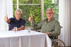 Счастливые старшие люди держа большие пальцы руки вверх стоковое изображение rf