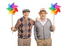 Счастливые старшие люди держа pinwheels стоковое изображение rf