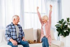 счастливые старшие пары играя шахмат дома стоковая фотография rf
