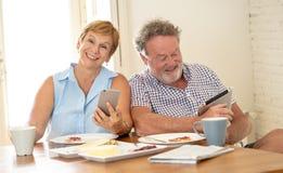 Счастливые старшие пары используя умные телефон и таблетку пока имеющ завтрак стоковое фото