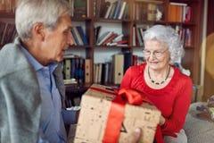 Счастливые старшие пары обменивая настоящие моменты на рождестве стоковое фото