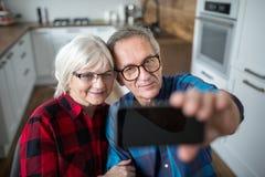 Счастливые старшие пары принимая selfie smartphone стоковое изображение
