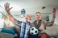 Счастливые старшие пары смотря футбол на ТВ стоковая фотография rf