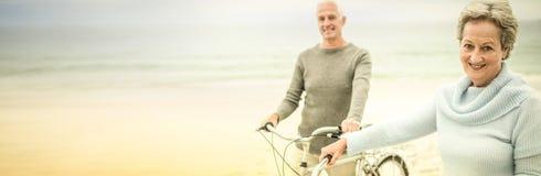 Счастливые старшие пары с их велосипедом стоковая фотография rf