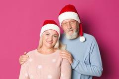 Счастливые старшие пары с шляпами рождества на предпосылке цвета Стоковое Изображение RF