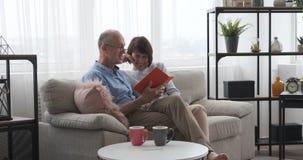 Счастливые старшие пары читая книгу на софе акции видеоматериалы