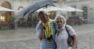 Счастливые старшие туристы стоят городскими и наслаждаются дождливой погодой в Львове акции видеоматериалы
