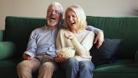 Счастливые старые пары держа дистанционное управление смеясь смотрящ тв-шоу акции видеоматериалы