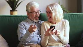 Счастливые старые пары держа смартфон смотря смеяться экрана акции видеоматериалы