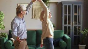 Счастливые старые старшие романтичные танцы пар в современной живущей комнате видеоматериал