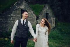 Счастливые стильные усмехаясь пары идя и целуя в Исландии, дальше Стоковое фото RF
