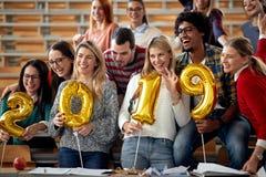 Счастливые студенты имея партию в университете стоковое фото