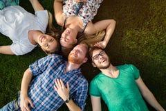 Счастливые студенты лежа на земле и усмехаться Стоковое фото RF