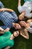 Счастливые студенты лежа на земле и усмехаться Стоковые Изображения RF