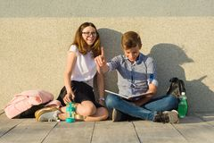 Счастливые студенты на тропе кампуса, подростки сидят на серой стене, прочитали учебники, выпивают воду, смотрят таблетку мальчик Стоковое Фото