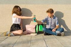Счастливые студенты на тропе кампуса, подростки сидят на серой стене, прочитали учебники, выпивают воду, смотрят таблетку Стоковые Изображения RF