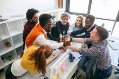 Счастливые студенты различных национальностей держа руки совместно стоковые фотографии rf