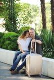 Счастливые туристы любят говорить пар на открытом воздухе, сидящ на стенде в парке города стоковое фото rf