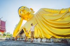 Счастливые туристы папа и сын на предпосылке ofLying статуя Будды стоковое фото