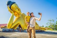 Счастливые туристы папа и сын на предпосылке ofLying статуя Будды стоковые фотографии rf