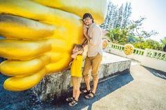 Счастливые туристы папа и сын на предпосылке ofLying статуя Будды стоковые изображения rf