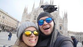 Счастливые туристы принимая автопортрет с телефоном перед собором Duomo, миланом Концепция туризма зимы акции видеоматериалы