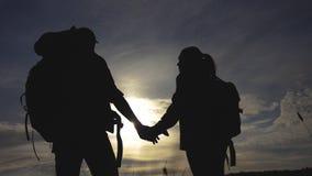 Счастливые туристы семьи идя держащ силуэт руки на заходе солнца концепция перемещения сыгранности hikers человек и женщина акции видеоматериалы