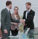 Счастливые усмехаясь бизнесмены тряся руки после дела в offi Стоковые Фото