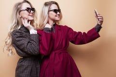 счастливые 2 усмехаясь девушки делая фото selfie на smartphone на бежевой предпосылке Стоковое Фото