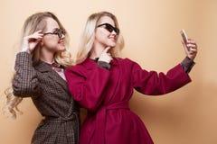 счастливые 2 усмехаясь девушки делая фото selfie на smartphone на бежевой предпосылке Стоковая Фотография RF